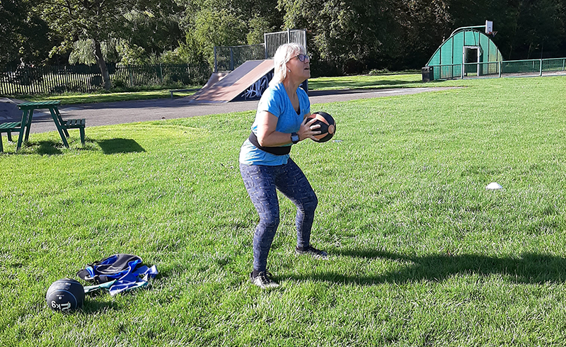 Woman with medicine ball. She is about to throw the ball
