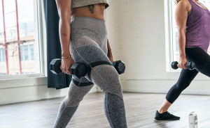 two women holding dumbbells performing a lunge
