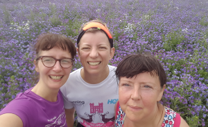 Three women smiling in front of a field of purple echium flowers